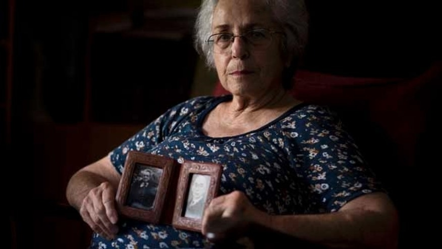 July 25, 2013: Cati Holland holds photos of her grandparents at her house in the Israeli city of Hadera.