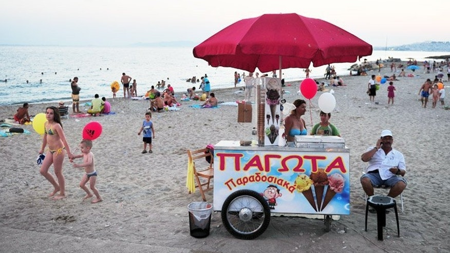 People cool off on a beach in Athens on July 11 last year. Foreign tourists are finding their way back to Greece's islands and ancient ruins, offering a rare boost to an economy contracting for the sixth year running.