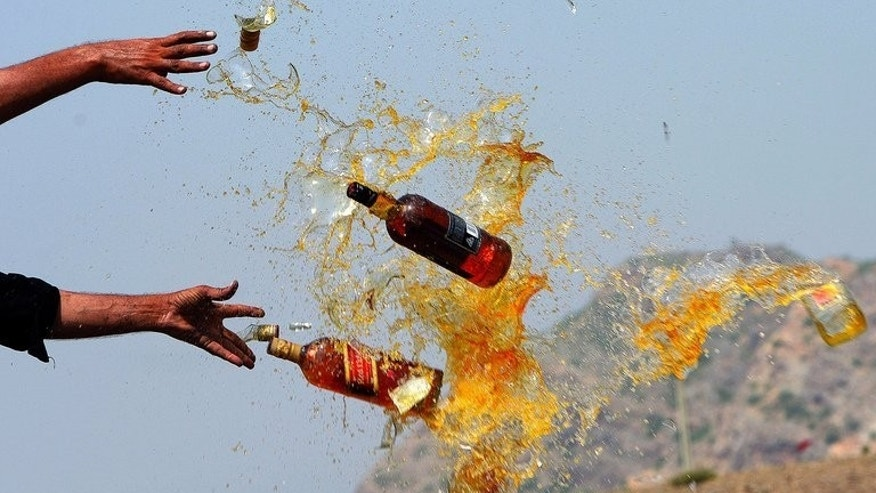 This file photo shows Pakistani officials destroying contraband alcohol, in the Shahkas area of the Jamrud Khyber Agency, on June 26, 2013. At least 18 people died and around two dozen others suffered serious health issues after partygoers at two separate events consumed toxic drinks in central Pakistan, officials said on Sunday.