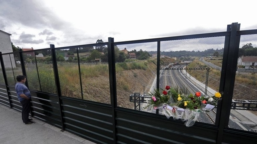 Flowers at the scene of the train crash in Santiago de Compostela, Spain, on July 27, 2013. The driver of the train that hurtled off the rails killing 78 people is to appear before a judge for questioning Sunday.