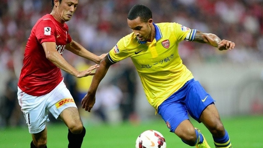 "Arsenal forward Theo Walcott (R) takes on Urawa Reds midfielder Kunimitsu Sekiguchi during the friendly on July 26, 2013. Arsenal have gone home on a positive note after what manager Arsene Wenger called a ""very difficult"" pre-season Asian tour in sweltering temperatures."