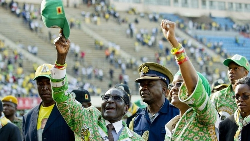 Zimbabwe's President Robert Mugabe (L) and his wife Grace (R) greet supporters after his address at a rally in Harare on July 28, 2013, ahead of elections on July 31. Mugabe on Sunday made his final call for peaceful voting as he vowed that the upcoming election will be free and fair.