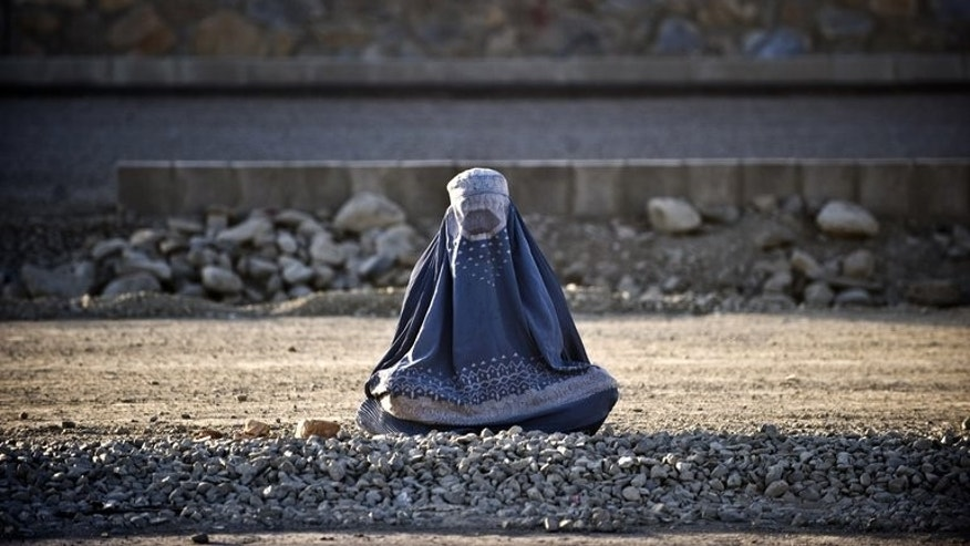 A burqa-clad woman sits on the roadside in Kabul on August 19, 2009. The fate of Afghanistan's women hangs in the balance as the 2014 withdrawal of international forces looms, a UN human rights watchdog warned Monday, denouncing a raft of abuses there.