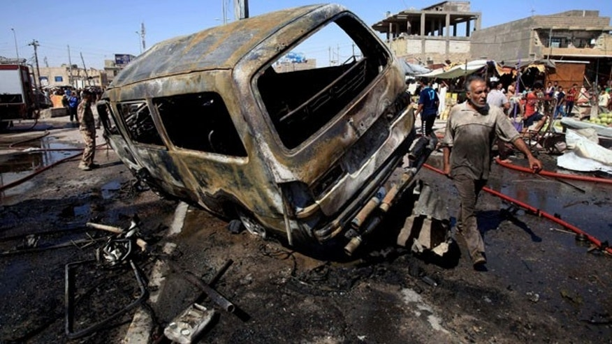 July 29, 2013: People and security forces inspect the site of a car bomb explosion in Basra, 340 miles southeast of Baghdad, Iraq.