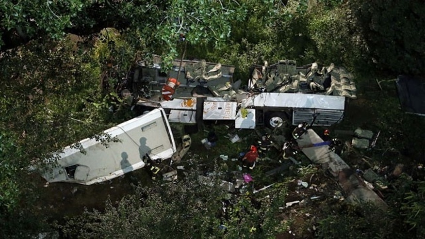 July 29, 2013: Firefighters work on the wreckage of a bus that plunged off the A16 highway near Avellino in southern Italy. (AP Photo)