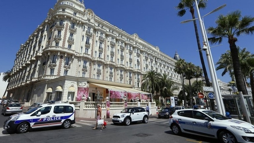 Police cars block the road outside the Carlton Hotel in the French Riviera resort of Cannes on July 28, 2013. An armed man who burst into the hotel stole jewels worth around $136 million (103 million euros), prosecutors said Monday, in one of the world's biggest jewellery thefts.