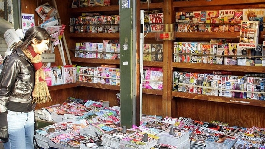 "A woman browses a selection of magazines on sale at a news stand in London in 2006. Retail chain the Co-operative has ordered the publishers of lad's magazines to hide their ""lewd"" covers or face seeing the magazines removed from shelves."