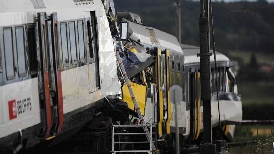 Two trains collided head-on July 29, 2013 in Granges-pres-Marnand, western Switzerland, injuring 35 passengers, at least five of them seriously, police said. Rescue workers at the site have found the body of one of the drivers, police said early Tuesday.