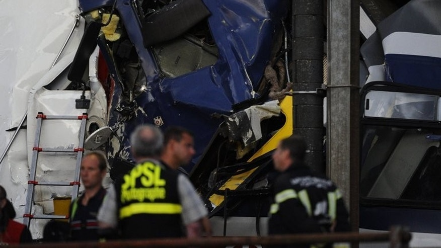 Rescuers work at the site of a train accident on July 29, 2013 in Granges-pres-Marnand, western Switzerland. Rescue workers at the site of the accident in which two trains collided, have found the body of one of the drivers, police said early Tuesday.