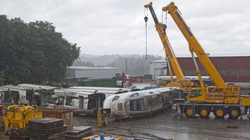 July 28, 2013: Part of the wreckage of the crashed train is seen in a crane depository on the outskirts of Santiago de Compostela, Spain. (AP Photo)