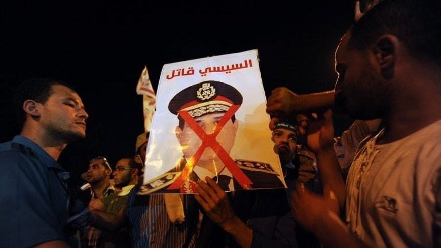 Egyptian supporters of deposed president Mohamed Morsi display a defaced poster of army chief General Abdel-Fattah al-Sisi during a demonstration in Cairo on July 30, 2013. The EU's foreign policy chief Catherine Ashton headed to meet Morsi early Tuesday as his supporters rallied anew in Cairo