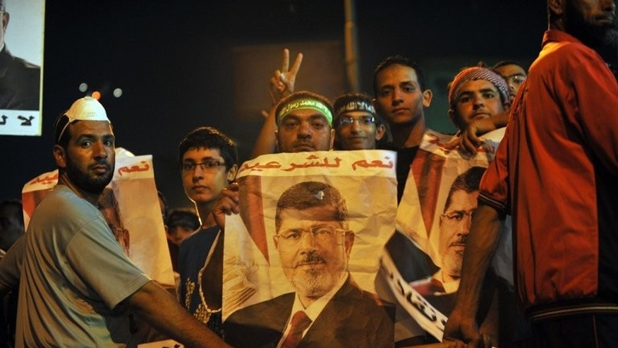 Egyptian supporters of deposed president Mohamed Morsi hold his picture during a demonstration in Cairo on July 30, 2013. The EU's foreign policy chief Catherine Ashton headed to meet Morsi early Tuesday as his supporters rallied anew in Cairo.