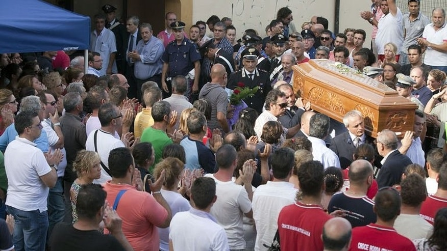 The coffin of a bus crash victim is carried out of the morgue on July 29, 2013 in Monteforte Irpino. Prime Minister Enrico Letta will join bereaved relatives at a mass funeral Tuesday for the 38 people killed in Italy when a coach plunged off a viaduct near Naples.