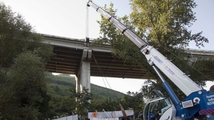 Workers remove the wreckage of the coach on July 29, 2013 near Baiano, southern Italy. The coach, carrying 48 people including children, rammed several cars after failing to break on a bend, smashing through a crash barrier and off the viaduct to plunge 30 metres (98 feet) down.