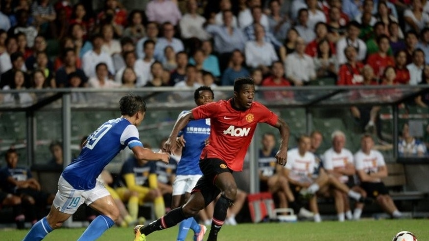 Danny Welbeck (right) of Manchester United runs for the ball against Hong Kong team Kitchee players during their friendly match at Hong Kong stadium on July 29, 2013. Manchester United saw off a spirited Kitchee 5-2 on Monday in Hong Kong to give David Moyes just his second victory as manager of the Premier League champions.