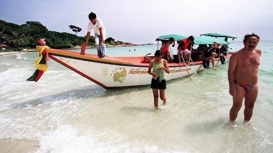 File picture shows a tour boat unloading tourists on a beach on the small resort island of Ko Samet some 200 kilometres southeast of Bangkok, October 26, 1998. Thai navy personnel battled on Monday to clean up a major oil slick which coated a beach on the popular tourist island in a national park after a pipeline leak.