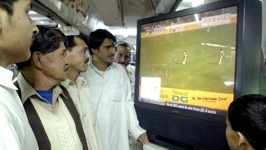 Pakistani men watch a television screen broadcasting a match between India and Pakistan in New Delhi at a shop in Quetta on April 17, 2005. Muneer Hussain, Pakistan's most famous cricket voice and a man credited with pioneering Urdu language commentary, has died after a prolonged illness.