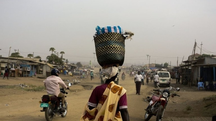 A woman walks through Gudele market in Juba, South Sudan. the country's security services have detained two Ugandan journalists who were filming in the capital Juba, officials said on Monday.
