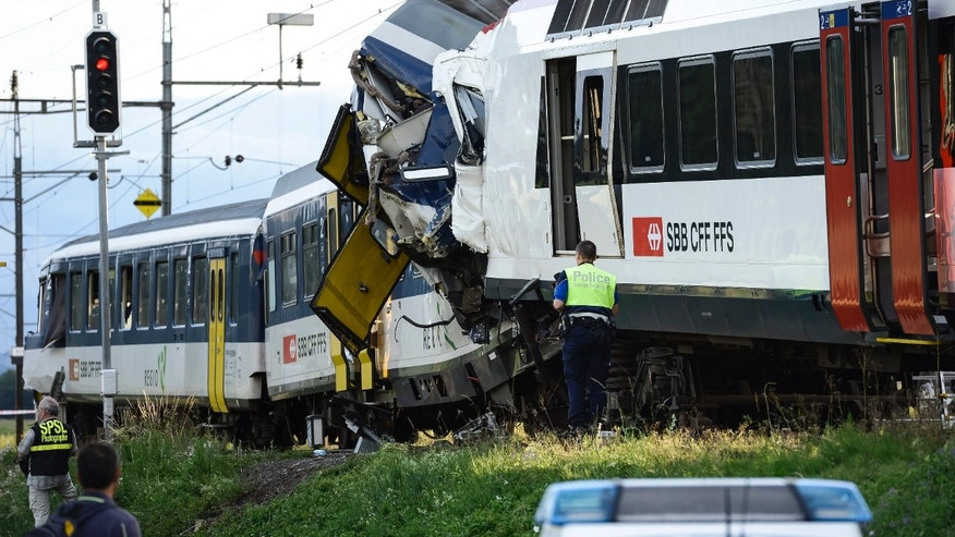 July 29, 2013 - Police inspect the site where two passenger trains collided head-on in Granges-pres-Marnand, western Switzerland. Dozens of people have been injured.
