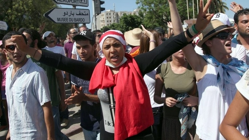 Protesters shout slogans against the ruling Ennahda party in Tunis after the funeral of Mohamed Brahmi on Saturday. Tunisia's Islamist-led government gathered in emergency meeting Monday as protesters demanding its ouster dug in outside parliament after another night of protests.