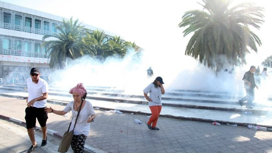 People run for cover as riot police fire tear gas amid clashes with protestors in Tunis on Saturday. Tensions have spiralled in Tunisia since the murder on Thursday of opposition MP Mohamed Brahmi, the second anti-Islamist figure gunned down in six months.