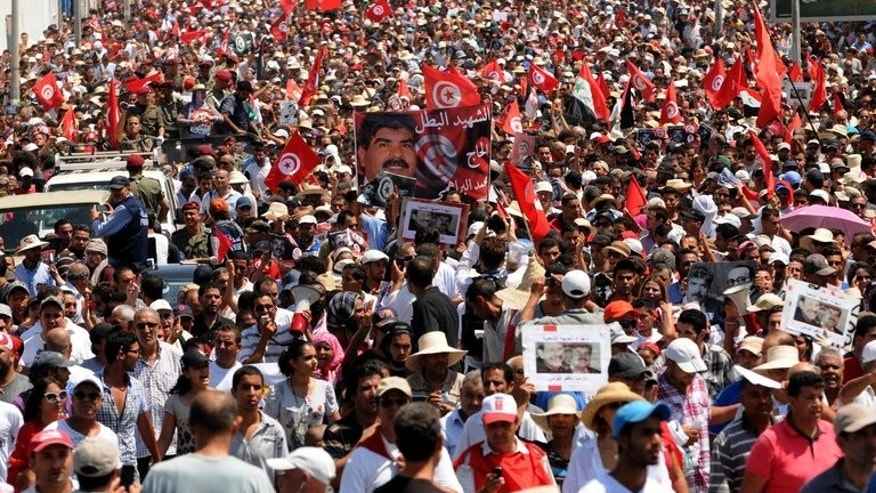 The funeral procession of Mohamed Brahmi after it leaves his home in the Tunis suburb of Ariana on Saturday. Many Tunisians blame the government for the two killings, particularly for failing to rein in radical Islamists accused of a wave of attacks since strongman Zine El Abidine Ben Ali was toppled in a popular uprising in 2011.