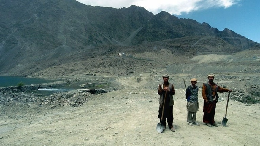 Picture taken July 13, 2004 shows three labourers with the mountains of the Himalayan Karakoram range in the background, on the outskirts of Skardu, some 300 kms north of Islamabad. Two New Zealand climbers have gone missing after an avalanche on the world's second-highest mountain, K2, in the Karakorams, a Pakistani official said Monday.