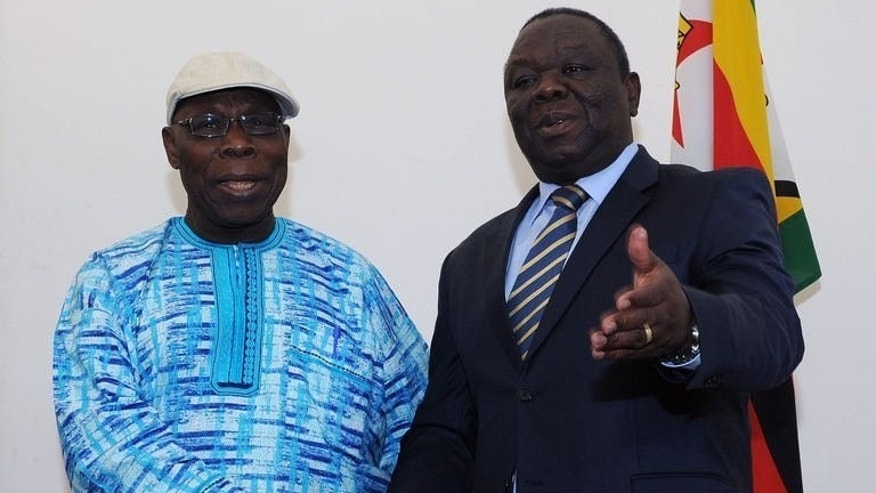 African Union (AU) Observer Mission chairperson Olusegun Obasanjo (L) poses for photos with Prime Minister of Zimbabwe Morgan Tsvangirai in Harare on July 29, 2013. With many international observers barred from covering Zimbabwe's crunch election Wednesday, two African blocs are becoming the eyes and ears of the world in a stern test of their credibility.