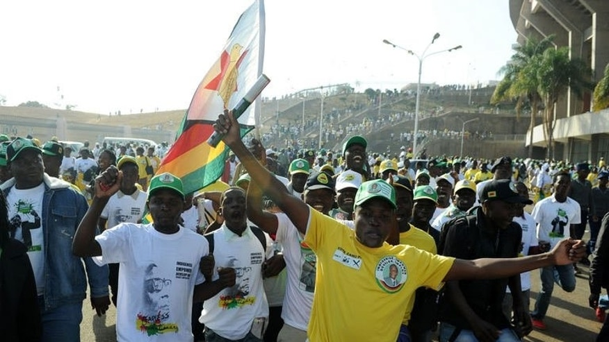 Supporters of Zimbabwe's President Robert Mugabe wave a Zimbabwean flag as they leave an election rally in Harare on July 28, 2013. Zimbabweans go to the polls on July 31 to choose between veteran President Robert Mugabe and long-time rival Morgan Tsvangirai.
