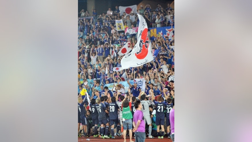 "Japan players celebrate with their supporters after beating South Korea in the East Asian Cup football match in Seoul on July 28, 2013. The Korea Football Association (KFA) issued a statement Wednesday insisting that Japanese fans waving a large ""rising sun"" Japanese military flag had incited South Korean supporters at Sunday's East Asia Cup tie in Seoul."