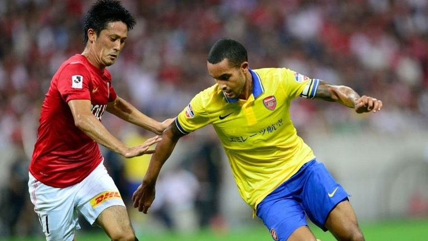 Arsenal forward Theo Walcott (R) battles for the ball with Urawa Reds midfielder Kunimitsu Sekiguchi (L) in Tokyo, on July 26, 2013. Arsenal, Chelsea, Liverpool, Spurs, Sunderland and Manchester rivals United and City, have all been in Asia on lucrative pre-season trips that did not include mainland China.