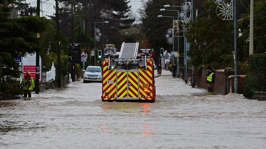 "Fire crews pumped water out of properties in the West Yorkshire town of Todmorden after a ""torrential"" downpour caused flash floods. File picture for illustration only shows a fire engine moving along a flooded road."