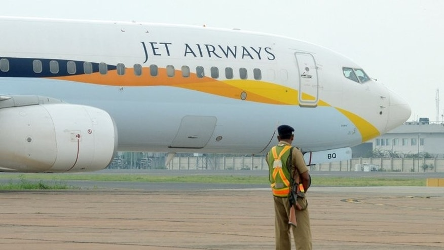 An Indian security official looks on as a Jet Airways passes at Indira Gandhi International Airport in New Delhi on September 12, 2012. Shares of India's private carrier Jet Airways jumped nearly eight percent Tuesday morning, a day after it was granted conditional approval to sell a stake worth $349 million to Abu Dhabi-based Etihad.