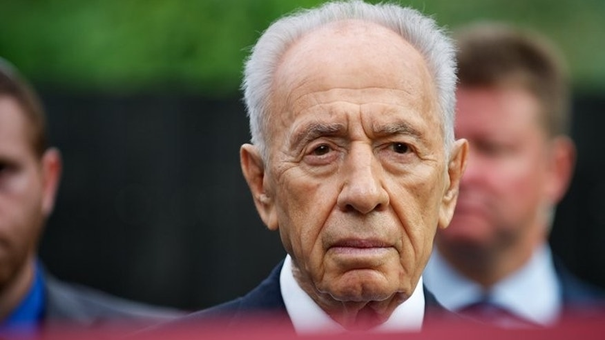 Israeli President Shimon Peres is pictured behind a red ribbon during the opening ceremony of the Zanis Lipke memorial in Riga, Latvia, on July 30, 2013.