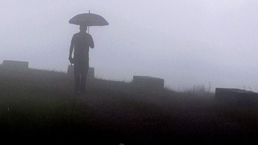 "A pedestrian walks through heavy fog at Mawsynram village in the north-eastern Indian state of Meghalaya, June 21, 2013, considered the ""wettest place on earth"" according to the Guinness World Records authority. Villagers use grass to sound-proof their huts from deafening rain and clouds are a familiar sight inside homes."