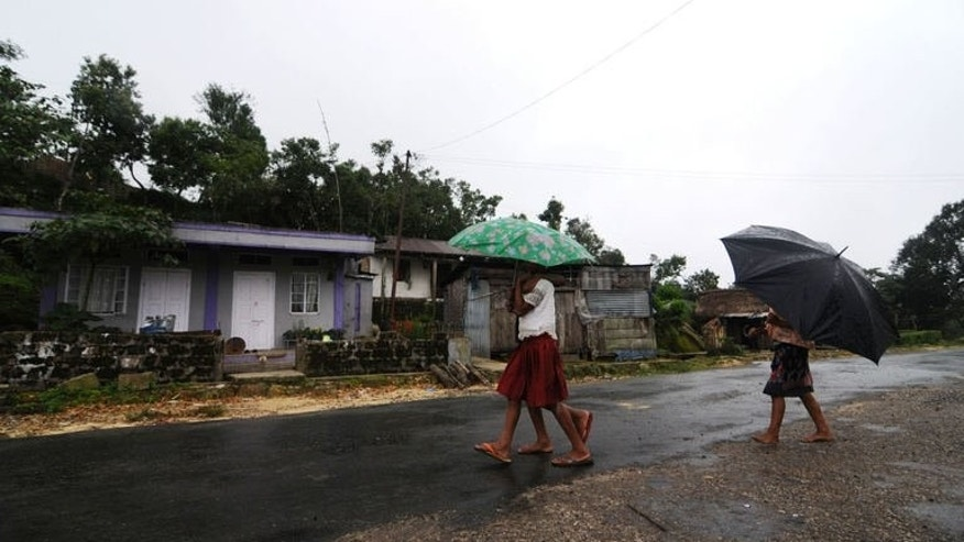 "In this photograph taken on June 21, 2013, children hold umbrellas as they walk through rain at Mawsawa village near Mawsynram in the north-eastern Indian state of Meghalaya and considered the ""wettest place on earth"" according to the Guinness World Records authority."