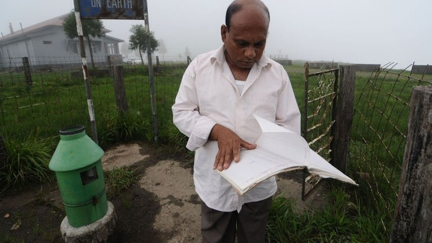 "In this photograph taken on June 21, 2013, technician, Ramkrishna Sharma, 53, in-charge of the rain-measuring looks at his log book at Mawsynram village in the north-eastern Indian state of Meghalaya and considered the ""wettest place on earth"" according to the Guinness World Records authority."
