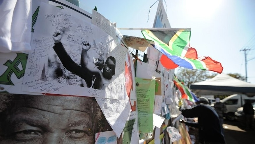 Tributes to Nelson Mandela are seen outside the hospital in Pretoria where he is staying, on July 19, 2013. Mandela continues to show signs of improvement after two months of hospital treatment, the South African presidency said, but gave no details of his condition after reported scares.