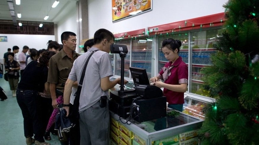Shoppers line up to buy snacks and drinks at a supermarket in Pyongyang on July 28, 2013. There are not many places to spend money in the capital Pyongyang. As a foreigner, the choice is reduced further by the need to find somewhere that takes foreign currency and -- importantly - is capable of giving change.