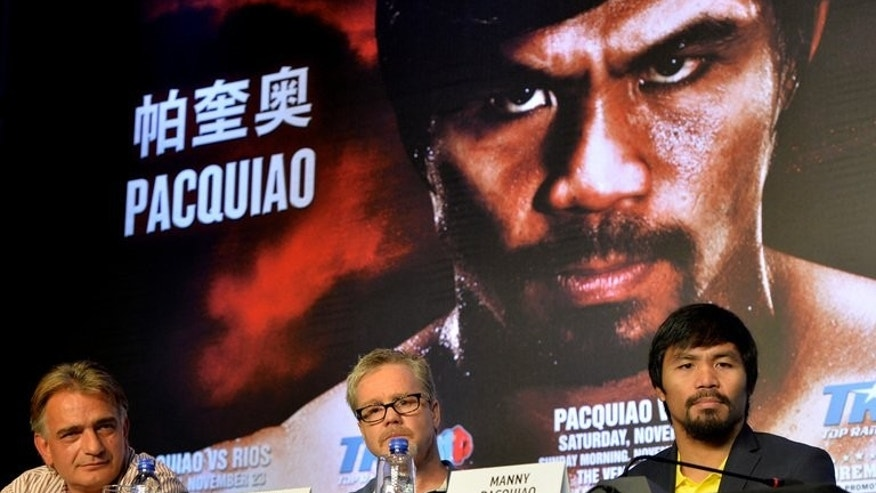 Manny Pacquiao (right) and trainer Freddie Roach at a press conference in Beijing on Tuesday. Philippine boxing hero Pacquiao has no immediate plans to run for president, his chief aide said Tuesday, following a fierce political backlash to comments he wanted to lead his country.