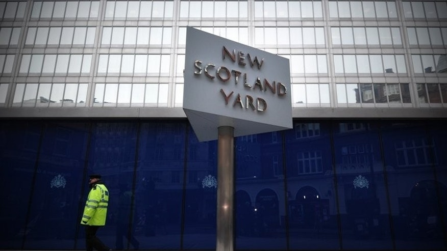 An officer walks past New Scotland Yard, in central London January 11, 2013. Police say they are investigating violent and sexually explicit Twitter postings directed at an MP in a growing row over threats to women on the social network.