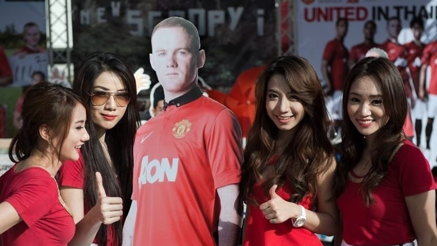 "Promotion models pose for a photo next to a life-size cardboard image of Manchester United's Wayne Rooney, near Rajamangala stadium, ahead of United's training session in Bangkok, on July 12, 2013. Rooney said he was ""gutted"" after a hamstring injury forced him out of United's Asian tour on the very first day with questions still unanswered about his future with the club."