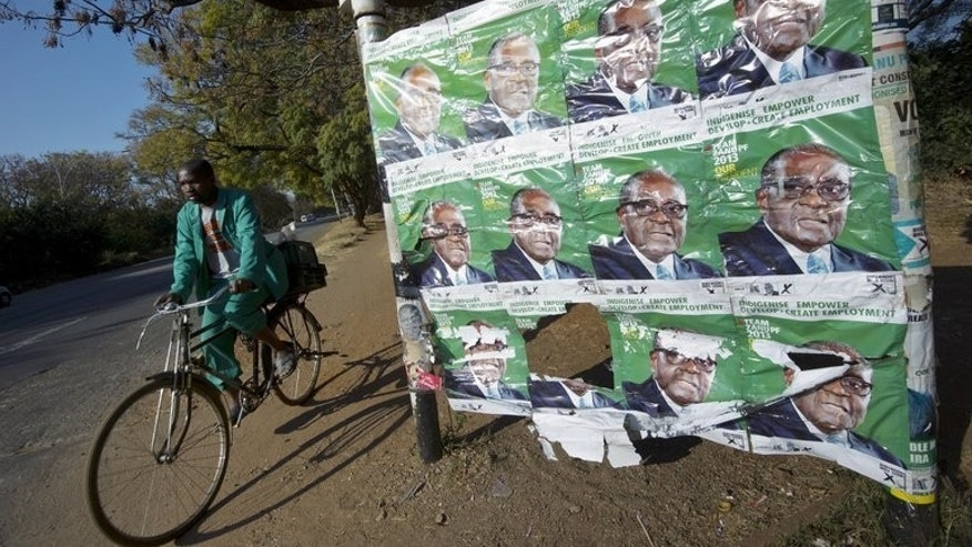 A Zimbabwean cycles past posters of Robert Mugabe in Harare on July 30, 2013. Supporters of the veteran president have voiced confidence that his 33-year-rule will be extended, when Zimbabweans vote in elections that many opponents fear will be rigged.