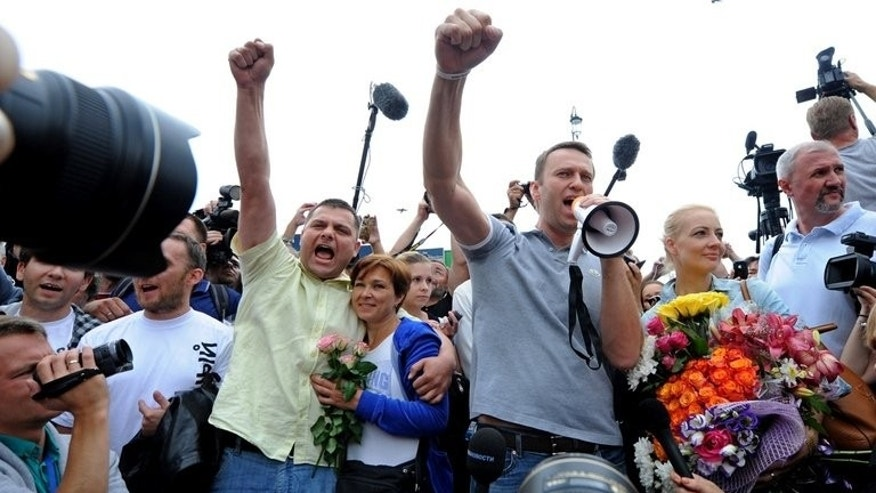 Russia's top opposition leader Alexei Navalny (C-R), flanked by his wife Yulia and his former colleague Pyotr Ofitserov (L), address supporters and journalists upon his arrival at a Moscow's railway station, on July 20, 2013. Both men were freed pending appeals of their prison sentences.