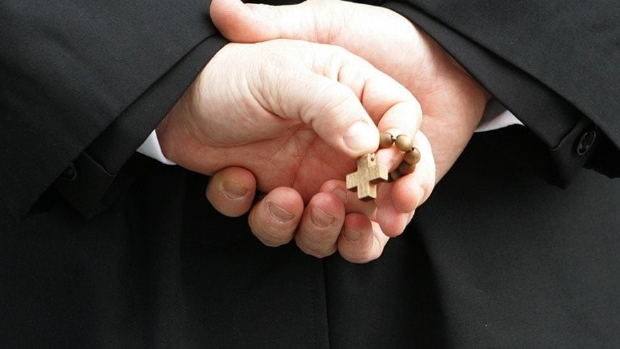 A priest in Rome holds a rosary on February 27, 2005. Scottish police are investigating claims of physical and sexual abuse at one of Scotland's best known Catholic boarding schools.