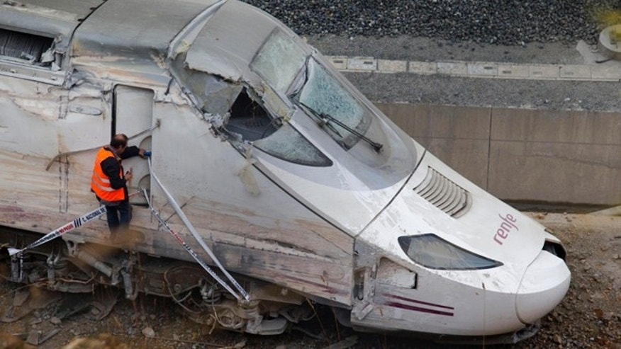 In this July 25, 2013 file photo, a rail personnel worker checks the cabin of a derailed train following an accident in Santiago de Compostela, Spain.