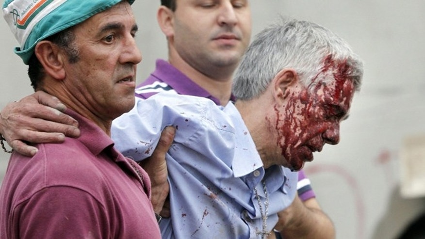 July 24, 2013: Train driver Francisco Jose Garzon Amo is helped by two men as he is evacuated from the site of a train accident in Santiago de Compostela, Spain.