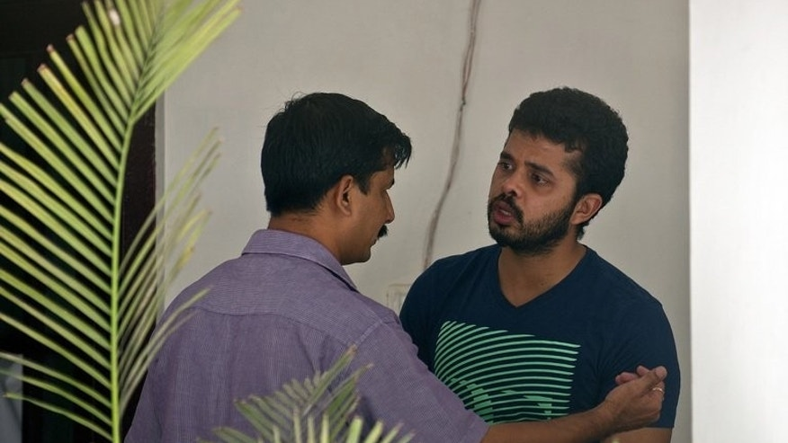 A Delhi police official (left) speaks to Shanthakumaran Sreesanth at the courthouse in New Delhi on May 28. Indian prosecutors charged fast bowler Shantakumaran Sreesanth and 38 others on Tuesday with links to organised crime and cheating over their alleged involvement in spot-fixing in the Indian Premier League, a lawyer said.