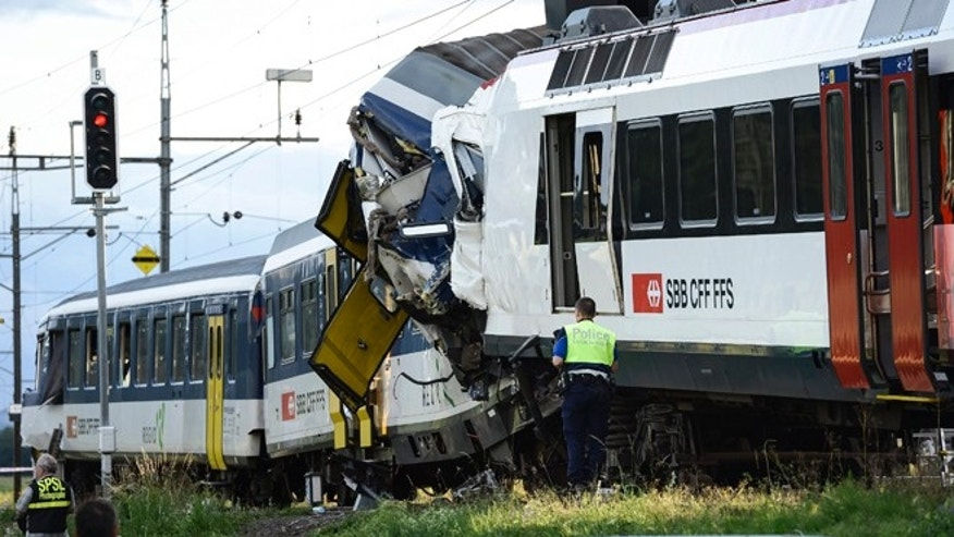 July 29, 2013: Police inspect the site where two passenger trains collided head-on in Granges-pres-Marnand, western Switzerland. Numerous people have been injured.