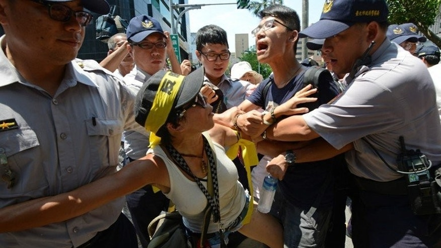 "Police clash with protesters opposing trade between Taiwan and China outside parliament in Taipei on July 30, 2013. Chanting ""Opposing the trade service agreement, safeguarding sovereignty"", demonstrators attempted to push their way through a police cordon around parliament in Taipei."